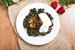 Boiled spinach on white dish with yogurt and wood decor, top view Kuvituskuvat