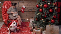 A young woman wrapping gifts with bulldog at xmas Stock Footage