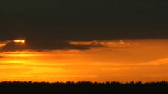 The sun leaves low overcast and comes for the horizon hiding behind clouds. Stock Footage