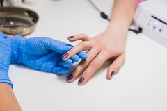 Nails painting with brush in nail salon Stock Photos