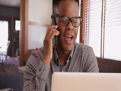 Black male with glasses talks on the phone working on his laptop Stock Footage