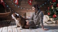 A pretty woman petting bulldog at xmas eve Stock Footage