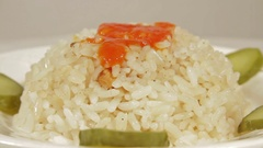 Rotating dish of rice with marinaded cucumbers Stock Footage