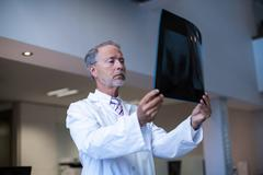 Male surgeon examining x-ray Stock Photos