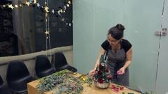 Brunette florist makes floral arrangement on table inside office Stock Footage