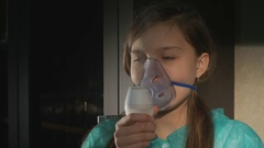 Girl with asthma problems making inhalation with mask on her face Stock Footage