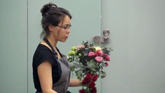Florist with all concentration collects flowers in bouquet Stock Footage