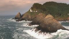 Aerial view of waves crashing on rocks below Heceta Head Lighthouse. Stock Footage
