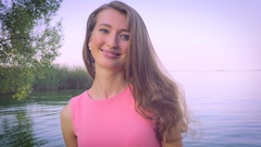 The girl with white skin near the water beautiful smiles and plays with his hair Stock Footage
