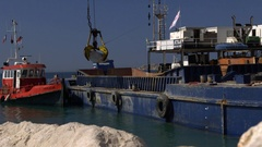 Crane lifts boulder for beach seawall defence barrier Stock Footage
