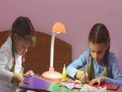 Two children doing crafts, one cuts with scissors colored cardboard Stock Footage