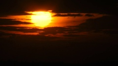 The sun moves down to a sunset in an aperture from dark clouds. Stock Footage