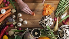Woman cutting carrot on wooden board in kitchen Stock Footage