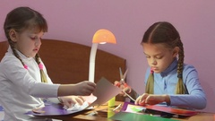 Two children cut with scissors pieces of colored paper, making crafts Stock Footage