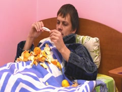 A sick man lying in bed, measuring the temperature and eats tangerines Stock Footage