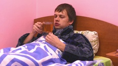 A sick man lying in bed and drink hot tea Stock Footage