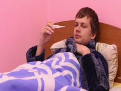 A sick man lying in bed and will measure the temperature of an electron Stock Footage