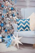 Christmas home interior - a cozy armchair and decorated fir in blue  white Stock Photos