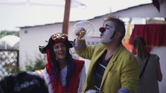 Man in clown costume make big soap bubbles on terrace of restaurant. Event Stock Footage