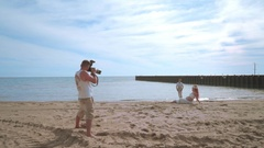 Photographer take photo of love couple on beach. Photo shooting Stock Footage