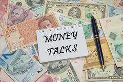 Notebook page with text MONEY TALKS, background from different world Currencies Stock Photos