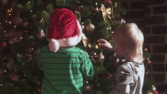 Two boys decorating a Christmas tree Stock Footage