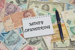 Notebook page with text MONEY LAUNDERING, background from different world Curren Stock Photos
