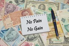 Notebook page with text NO PAIN NO GAIN, background from different world Currenc Stock Photos