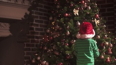 A boy decorating a Christmas tree Stock Footage