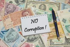 Notebook page with text NO CORRUPTION, background from different world Currencie Stock Photos