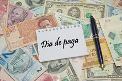 """Notebook page with SPANISH text """"DIA DE PAGA"""" (PAYDAY), background from differe Stock Photos"""