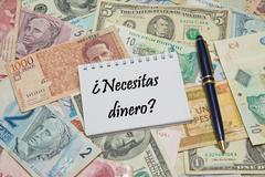 """Notebook page with SPANISH text """"NECESITAS DINERO"""" (NEED MONEY), background from Stock Photos"""