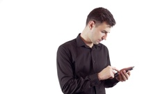 Laughing young man in black shirt talking by mobile phone over white background Stock Footage