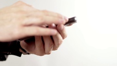 Hands swipe to text on an cellphone. The background is clean white Stock Footage