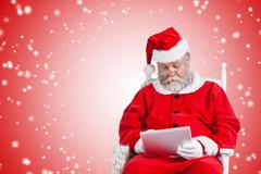 Composite image of santa claus watching movie on digital tablet Stock Photos