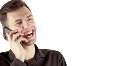 Close up portrait of laughing young man in black shirt talking by mobile phone Stock Footage