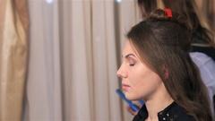 Makeup artist gets paint on eyelids of model Stock Footage