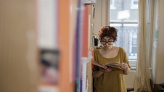 4K Portrait smiling student standing next to bookcase in shared accommodation Stock Footage