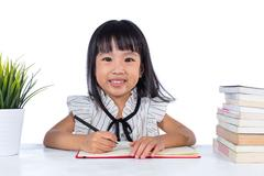 Smiling Asian Chinese little office lady writing book Stock Photos