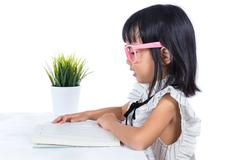 Smiling Asian Chinese little girl reading book Stock Photos