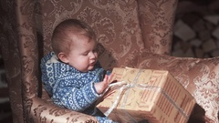 Baby boy sitting on chair with xmas gifts Stock Footage