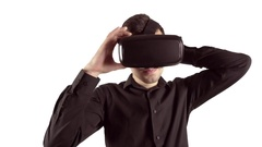 Man trying to put on his virtual reality goggles. Studio video, white background Stock Footage