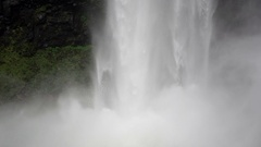 Static close up shot of a waterfall crashing down into a body of water Stock Footage