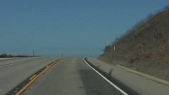 Driving north on PCH hwy 1 cresting to see ocean tight shot Stock Footage