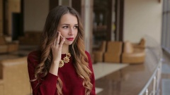 Upset woman in the red sweater talking on the phone near the window. Stock Footage