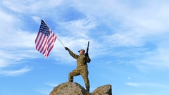 Soldier on mountain top with automatic rifle,  and  American Flag. Slow Motion Stock Footage