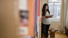 4K Students reading & choosing book from bookcase in shared accommodation Stock Footage