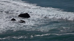 Slo mo breaking wave coming in splashing up over rock 2 Stock Footage
