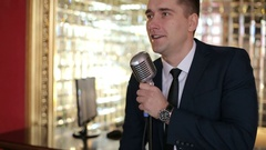 Man in elegant black jacket and white shirt says in a retro microphone. Stock Footage