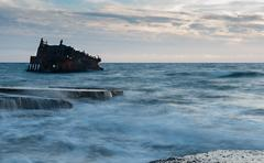 Shipwreck of an abandoned ship on a rocky shore Stock Photos